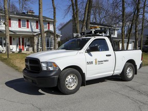 A truck from the Beaconsfield public works department drives up streets in the West Island suburb of Montreal broadcasting a social distancing reminder on April 6, 2020.