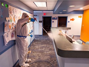 A Paul Davis Restoration Inc. employee disinfects a countertop at an undisclosed location.