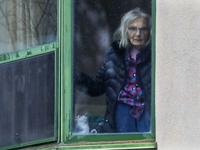 A woman looks out the window of a room at Résidence Herron in Dorval on Monday April 13, 2020.