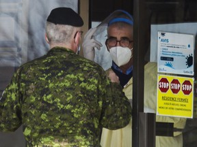 A Canadian Armed Forces member talks with a worker at a Laval seniors residence after meeting with staff there with other  Canadian military members in Laval near Montreal Sunday, April 19,2020. The military is deploying 125 medical workers in CHSLDs, hard hit by COVID-19.