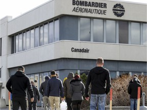 Workers return from lunch to the Bombardier plant on Marcel-Laurin Blvd.  in 2018. The company said it has started recalling most of its 11,000 Canadian aviation and transportation employees that were furloughed because of the pandemic.
