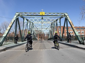 Montreal police officers on bicycle patrol the now-closed Charlevoix Bridge as the city deals with the coronavirus pandemic April 6, 2020. The Atwater foot bridge was closed over the weekend, requiring pedestrians to detour to the Charlevoix Bridge.