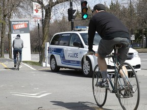 A cyclist passes next to a Montreal police cruiser at the entrance of Maisonneuve Park on Sunday May 3, 2020. The parking lot was closed to cars on Sunday to prevent overcrowding of the park.