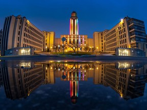 The University of Montreal, reflected in a puddle, lit their centre tower in rainbow lights April 29, 2020.