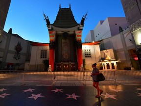 A woman walks past the closed courtyard of Hollywood's iconic TCL Chinese Theater, famed for the hand and foot prints of movie stars. Montreal film industry players are pushing to reopen cinemas mid-June or July.