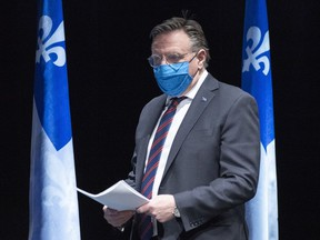 Quebec Premier Francois Legault arrives at a news conference wearing a protective mask in Montreal on May 14, 2020.