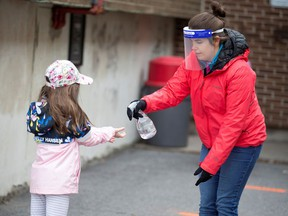 A student has her hands sanitized in the schoolyard, as schools outside the greater Montreal region begin to reopen their doors amid the coronavirus disease (COVID-19) outbreak, in Saint-Jean-sur-Richelieu, Quebec, Canada May 11, 2020. REUTERS/Christinne Muschi/File Photo