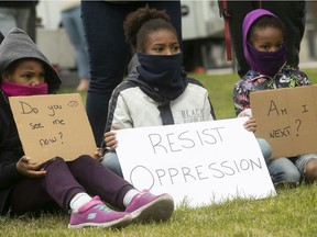 Young protesters hold signs during anti-racist and anti-police brutality demonstration in Montreal on May 31, 2020.