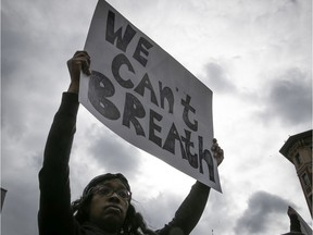 A protester holds up sign during an anti-racist and anti-police brutality demonstration on Sunday May 31, 2020.
