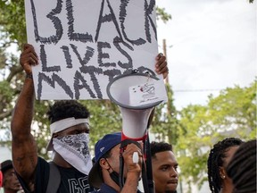 Alouettes running-back James Wilder Jr. holds a Black Lives Matter sign in Houston during a weekend protest.