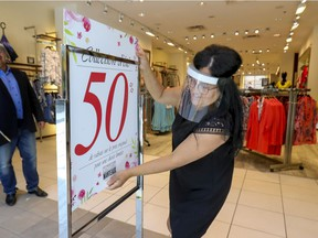 Saleswoman Nelly Kara installs a sale sign at the entrance to the Manteaux Manteau store in Fairview Pointe Claire shopping mall, west of Montreal Friday June 19, 2020.