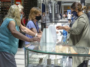 Mona Mansur, right, wears a mask behind a plexiglass barrier at her Arabella jewelry kiosk at Fairview Pointe-Claire shopping mall on Friday, June 19, 2020.