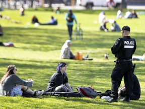 An SPVM officer speaks with people who gathered at a busy Jeanne-Mance Park on May 18 during the COVID-19 pandemic.