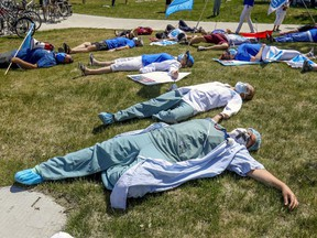 """Saying they're """"dead from fatigue,"""" health care workers hold a die-in during demonstration outside Maisonneuve-Rosemont Hospital in Montreal Wednesday May 27, 2020."""