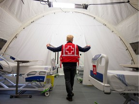 A volunteer with the Red Cross shows a doorway between beds in a mobile hospital set up in partnership with the Canadian Red Cross in the Jacques-Lemaire Arena back in April 2020 in Montreal.