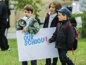 """Rocco (centre) and Max Dandenault listen as Matteo Osmond chants while students, parents and teachers formed a chain around General Vanier Elementary school in St-Léonard June 5, 2019. """"to save our school, raise awareness, solidarity, and raise school spirit."""" Their battle was ultimately unsuccessful."""