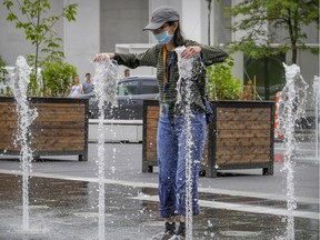 Julie Situ cools off in the fountain in Place des Festivals in Montreal Thursday July 2, 2020. (John Mahoney / MONTREAL GAZETTE)