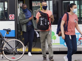 People disembark a bus at the Vendôme métro station in Montreal on July 13, 2020. Masks become mandatory on public transit in Quebec on Monday morning to stop the spread of COVID-19.