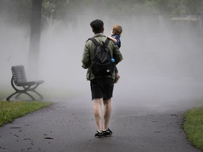 David Dionise carries his son, Henri, into the mist in Montreal, on Friday, July 17, 2020. (Allen McInnis / MONTREAL GAZETTE)