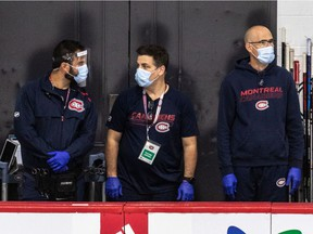 From left to right, Matthew Romano (assistant athletic therapist and physiotherapist), Patrick Langlois (assistant equipment manager) and Pierre Ouellette (assistant equipment manager) watch the Canadiens practise Thursday at the Bell Sports Complex in Brossard.