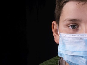 FILE: A child wears a surgical mask.