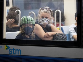 Rebecca and her son, Henri, ride the métro at the Berri-UQAM station in Montreal, on Tuesday, June 30, 2020. (Allen McInnis / MONTREAL GAZETTE)