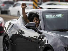 """A man shows his support during Sunday's """"driving while Black"""" convoy, protesting racial bias from police."""