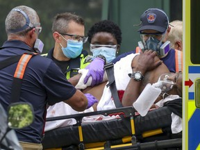 A man who police say was stabbed is loaded into an ambulance on Jeanne Mance St. in Montreal on Sunday, July 12, 2020.