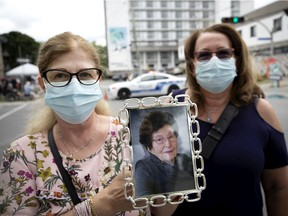 Sisters Sabina Lanzolla, left, and Nancy Lanzollo hold a picture of their mother, Giacomina Scattaglia-Lanzolla at a vigil for those that passed away from Covid-19 at Residence Angelica in Montreal, on Thursday, July 23, 2020. (Allen McInnis / MONTREAL GAZETTE)