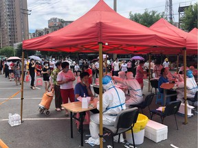 This file photo taken on July 26, 2020 shows people lining up to undergo COVID-19 coronavirus tests at a makeshift testing center in a car park in Dalian, in China's northeast Liaoning province. - China recorded 61 new coronavirus cases on July 27 -- the highest daily figure since April -- propelled by clusters in three separate regions that have sparked fears of a fresh wave. (Photo by STR / AFP) / China OUT