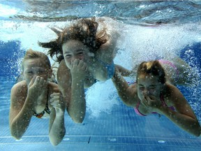 Three girls dive in a swimming pool.
