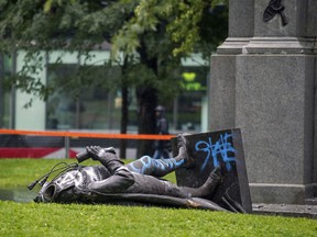 The headless body of the statue of Sir John A. Macdonald lies at the base of the monument from which it was pulled during a demonstration by the Coalition for BIPOC Liberation in Montreal on Saturday, Aug. 29, 2020.