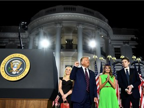 First Lady Melania Trump (2nd R), Barron Trump (R) and Tiffany Trump stand with US President Donald Trump as he pumps his fist after he delivered his acceptance speech for the Republican Party nomination for reelection during the final day of the Republican National Convention at the South Lawn of the White House in Washington, DC on August 27, 2020.