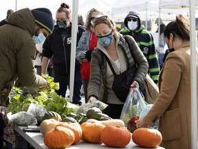 People line up for locally grown vegetables during the last session of the season at Marché Ste-Anne in Ste-Anne-de-Bellevue, on Saturday, Oct. 24, 2020.