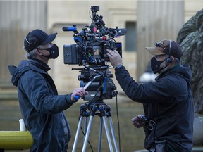 Two cameramen checking equipment during filming of The Batman movie outside St. George's Hall on October 14, 2020 in Liverpool, England. Filming began in January 2020 but was put on hold due to the Coronavirus pandemic.