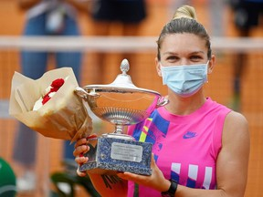 Romania's Simona Halep as she celebrates winning the final with the trophy after Czech Republic's Karolina Pliskova retired from the match after sustaining an injury at the Italian Open on Sept. 21, 2020, in Rome.