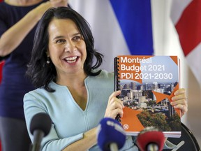 Montreal Mayor Valérie Plante holds up a copy of the city's budget for the coming year at a press conference on Thursday November 12, 2020.
