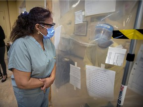 Annie Boto, left, head nurse in the hot zone, speaks with a co-worker through heavy plastic separating the nursing station from the halls at the Donald Berman Maimonides Geriatric Centre in Côte-St-Luc on Tuesday, November 24, 2020.