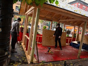 Workers build up an outdoor area outside a restaurant in New York on November 13, 2020. Bars and restaurants in New York will shut early on November 13 under fresh curbs designed to slow soaring Covid-19 infections as the number of daily deaths across the globe topped 10,000 for the first time since the pandemic began.