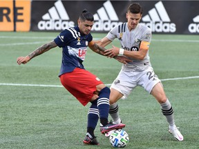Montreal Impact defender Jukka Raitala, right, and New England Revolution forward Gustavo Bou battle during the first half at Gillette Stadium in Foxborough, Mass., on Sept. 23, 2020