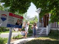 A client has her hands sanitized by a real estate agent at a visit to a house for sale in Montreal in June.