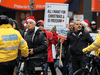 Unmasked people take part in a protest against COVID-19 restrictions in Toronto on December 20, 2020.