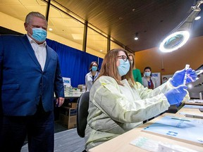 Ontario Premier Doug Ford watches a health-care worker prepare a Pfizer/BioNTech vaccine at the Michener Institute in Toronto Monday.