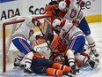 Montreal Canadiens players crowd the Edmonton Oilers' net and goalie Mikko Koskinen trying to jam in the puck at Rogers Place in Edmonton on Jan. 18, 2021.