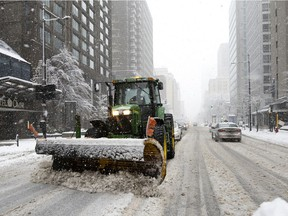 Snow-removal crews clear Sherbrooke St. in Montreal on Saturday, Jan. 16, 2021.