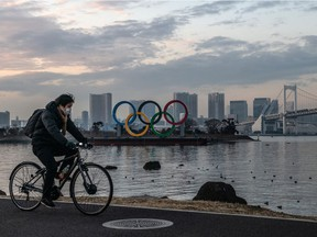 A man wearing a face mask cycles past the Olympic Rings on Friday, Jan. 22, 2021, in Tokyo.