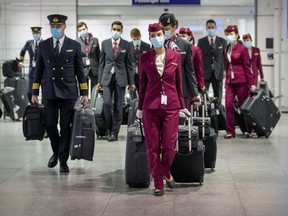 Qatar Airways flight crew walk through the arrivals area after landing at Trudeau airport in Montreal on Wednesday, Dec. 30, 2020.