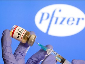 "FILE PHOTO: A woman holds a small bottle labeled with a ""Coronavirus COVID-19 Vaccine"" sticker and a medical syringe in front of the displayed Pfizer logo in this illustration taken Oct. 30, 2020."