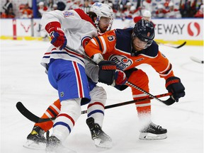 Montreal Canadiens centre Phillip Danault and Edmonton Oilers defencemen Adam Larssen battle for position during the second period at Rogers Place in Edmonton on Jan. 18, 2021.
