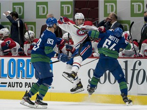 Canucks' Tyler Motte (64) checks Canadiens' Jesperi Kotkaniemi (15) as Vancouver forward Jay Beagle (83) looks on in the first period at Rogers Arena on Saturday, Jan 23, 2021, in Vancouver.